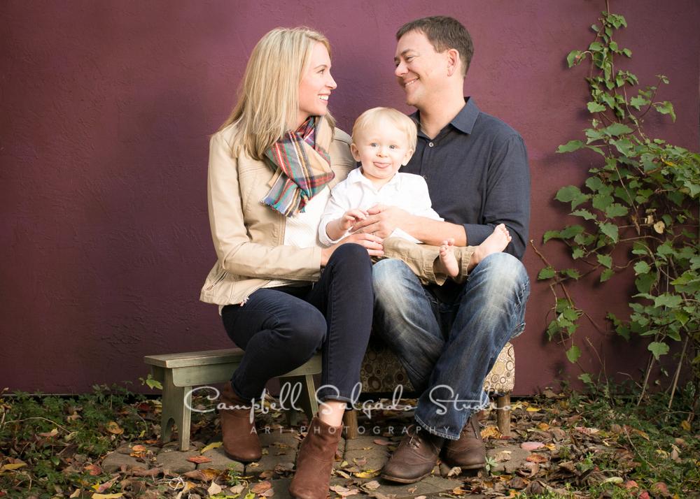 Portrait of family on plum stucco backgroundby family photographers at Campbell Salgado Studio, Portland, Oregon.