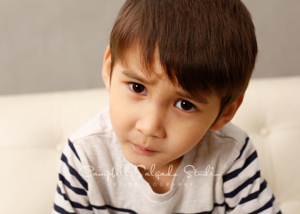 Portrait of boy on modern gray backgroundby children'sphotographers at Campbell Salgado Studio, Portland, Oregon.