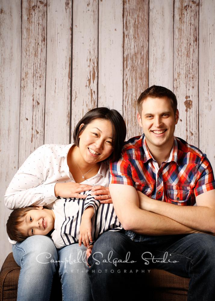 Portrait of family on white fenceboards backgroundby family photographers at Campbell Salgado Studio, Portland, Oregon.