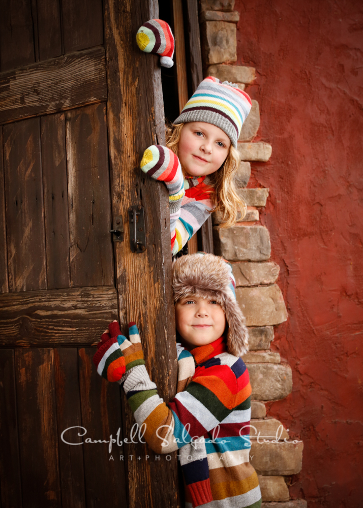 Portrait of kids on rustic door backgroundby childrensphotographers at Campbell Salgado Studio, Portland, Oregon.