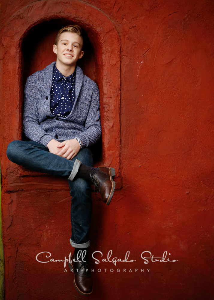 Portrait of teen on red stucco background by family photographers at Campbell Salgado Studio, Portland, Oregon.