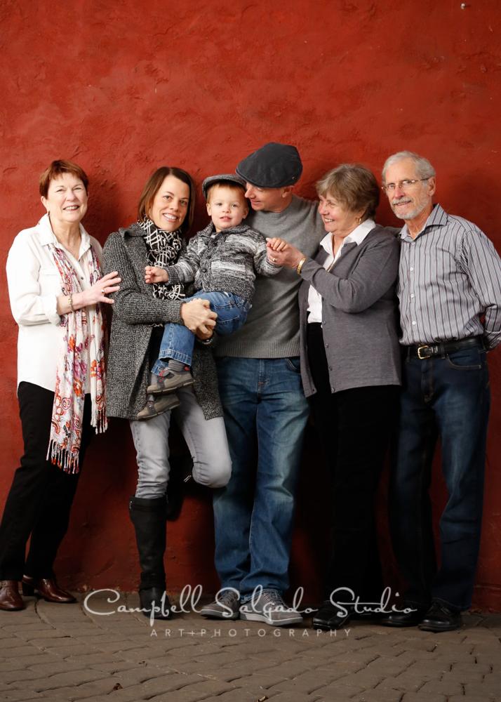 Portrait of family on red stucco backgroundby family photographers at Campbell Salgado Studio, Portland, Oregon.