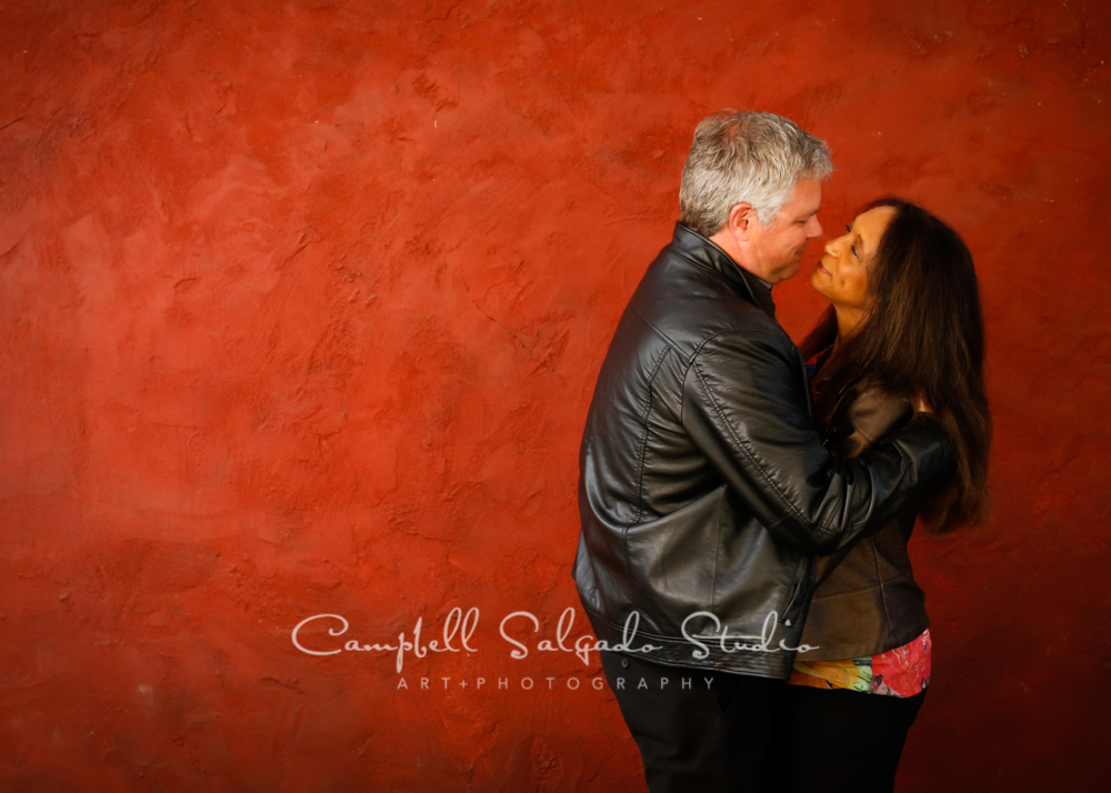 Portrait of couple on red stucco background by couples photographers at Campbell Salgado Studio, Portland, Oregon.