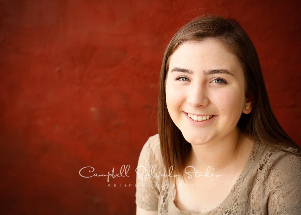 Portrait of girl on red stucco backgroundby family photographers at Campbell Salgado Studio, Portland, Oregon.