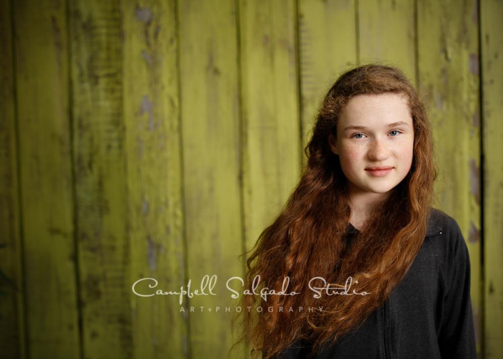Portrait of girlongreen fence boardbackgroundby childphotographers at Campbell Salgado Studio, Portland, Oregon.