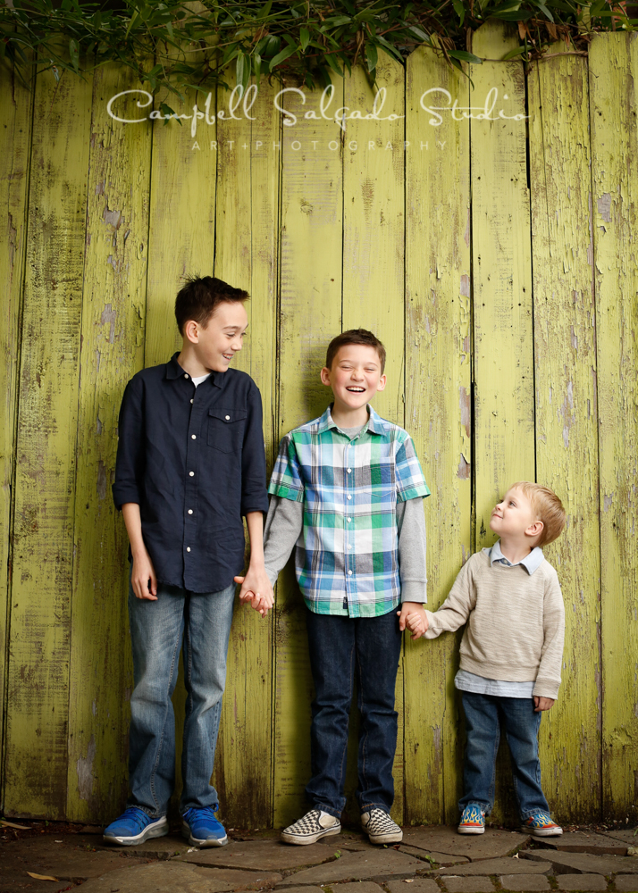 Portrait of kids on lime fence boards background by child photographers at Campbell Salgado Studio, Portland, Oregon.