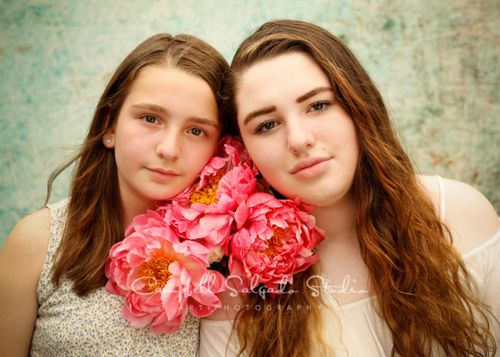 Portrait of sisters on weathered green background by family photographers at Campbell Salgado Studio, Portland, Oregon.