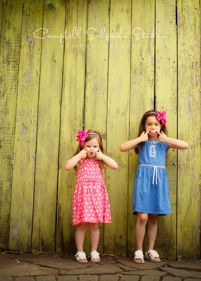 Portrait of sisterson lime fence boards backgroundby family photographers at Campbell Salgado Studio, Portland, Oregon.