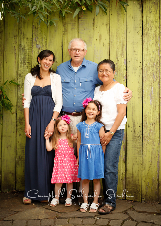 Portrait of multi-generational family on lime fence boards backgroundby family photographers at Campbell Salgado Studio, Portland, Oregon.