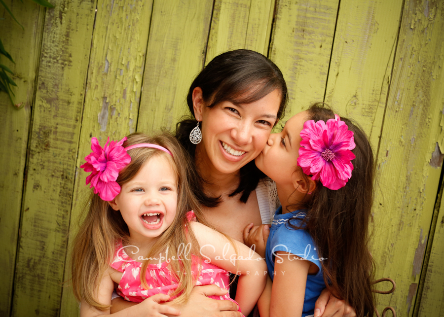 Portrait of mother and daughters on lime fence boards backgroundby family photographers at Campbell Salgado Studio, Portland, Oregon.