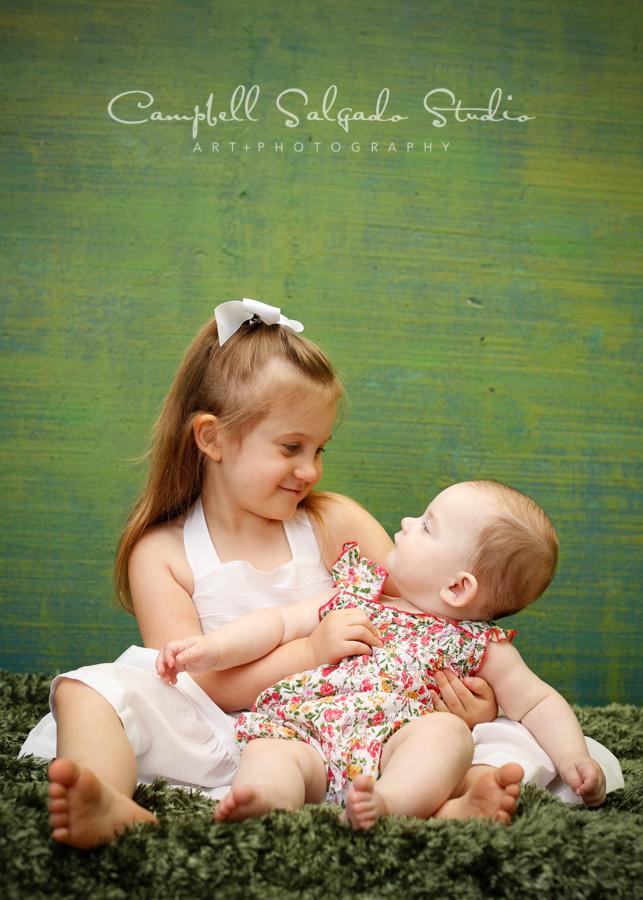 Portrait of sisters on green weave backgroundby childrens photographers at Campbell Salgado Studio, Portland, Oregon.