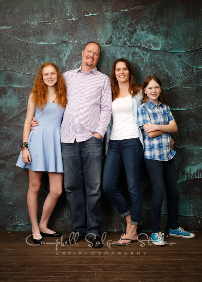 Portrait of family on copper wave background by family photographers at Campbell Salgado Studio.