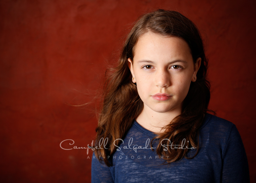 Portrait of girl on red stucco background by children's photographers at Campbell Salgado Studio in Portland, Oregon.