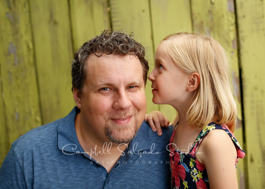 Portrait of father and daughter on lime fenceboards background by family photographers at Campbell Salgado Studio in Portland, Oregon.