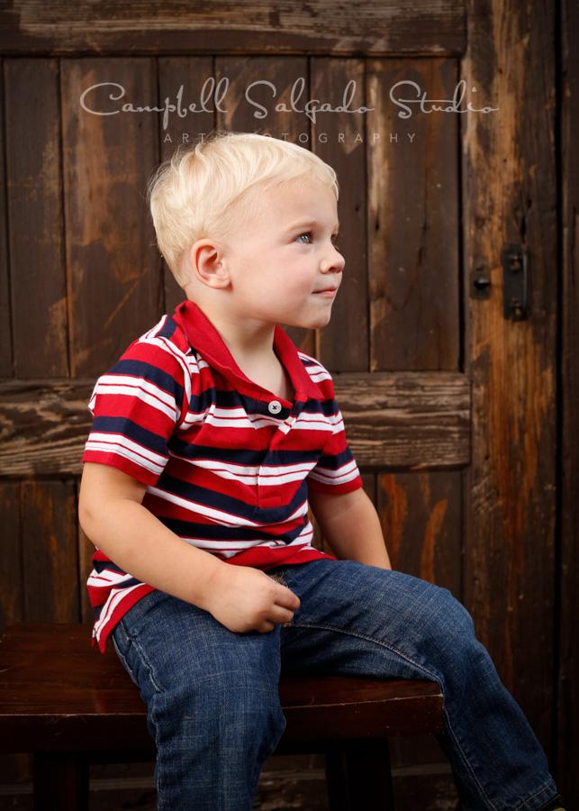 Portrait of toddler on rustic door background by children's photographers at Campbell Salgado Studio in Portland, Oregon.