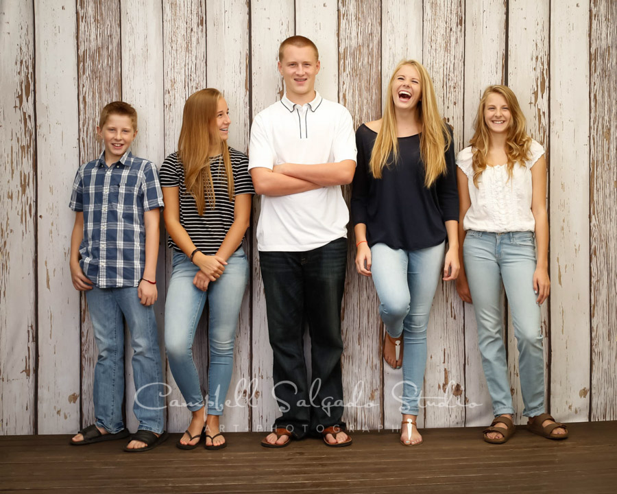 Portrait of siblings on white fence boards background by family photographers at Campbell Salgado Studio in Portland, Oregon.