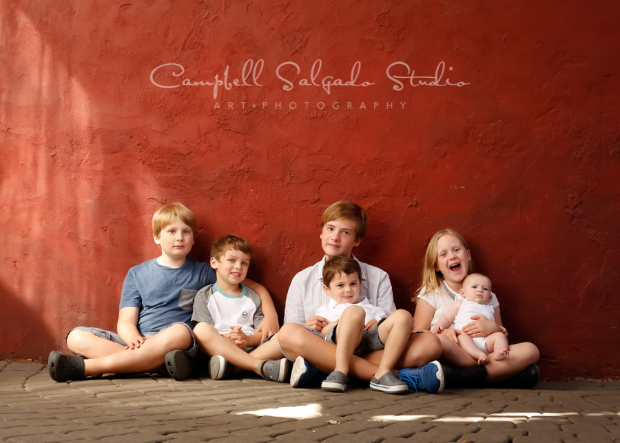 Portrait of children on red stucco background by children's photographers at Campbell Salgado Studio in Portland, Oregon.