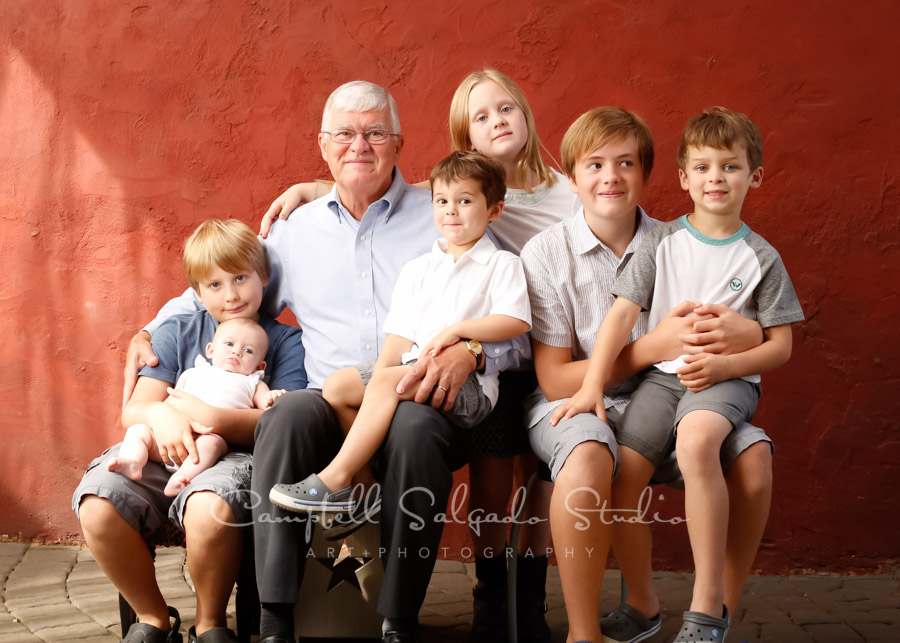Portrait of multi-generational family on red stucco background by family photographers at Campbell Salgado Studio in Portland, Oregon.
