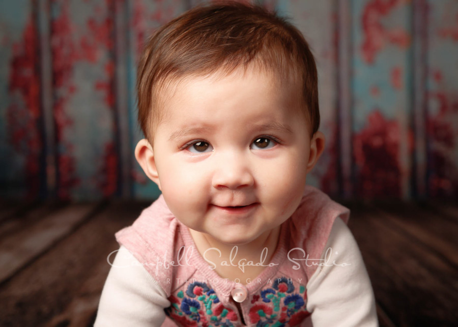 Portrait of baby on Italian rust background by childrens photographers at Campbell Salgado Studio in Portland, Oregon.