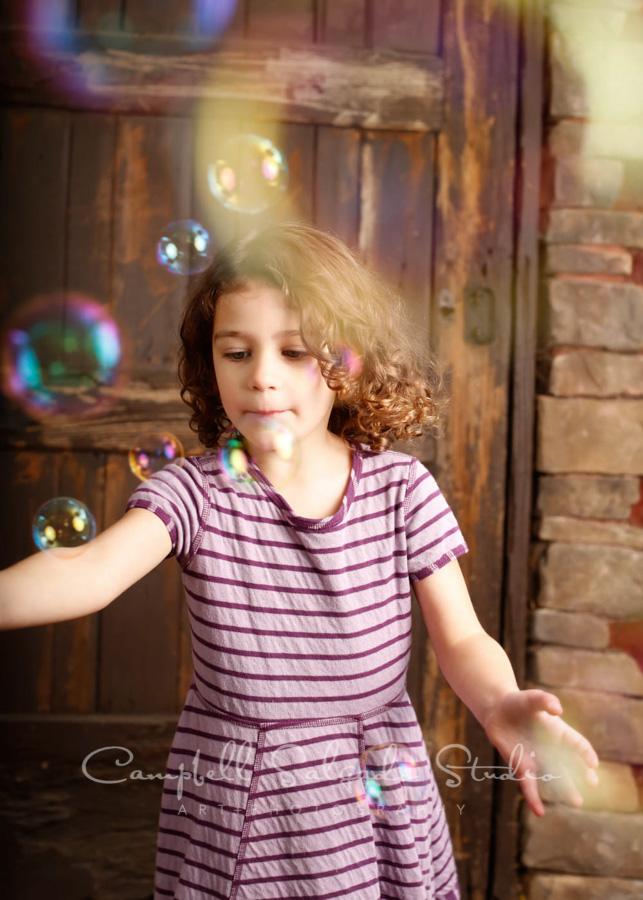 Portrait of girl on rustic door background by children's photographers at Campbell Salgado Studio in Portland, Oregon.