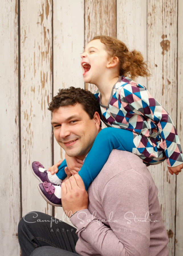 Portrait of father and daughter on white fenceboards background by family photographers at Campbell Salgado Studio in Portland, Oregon.
