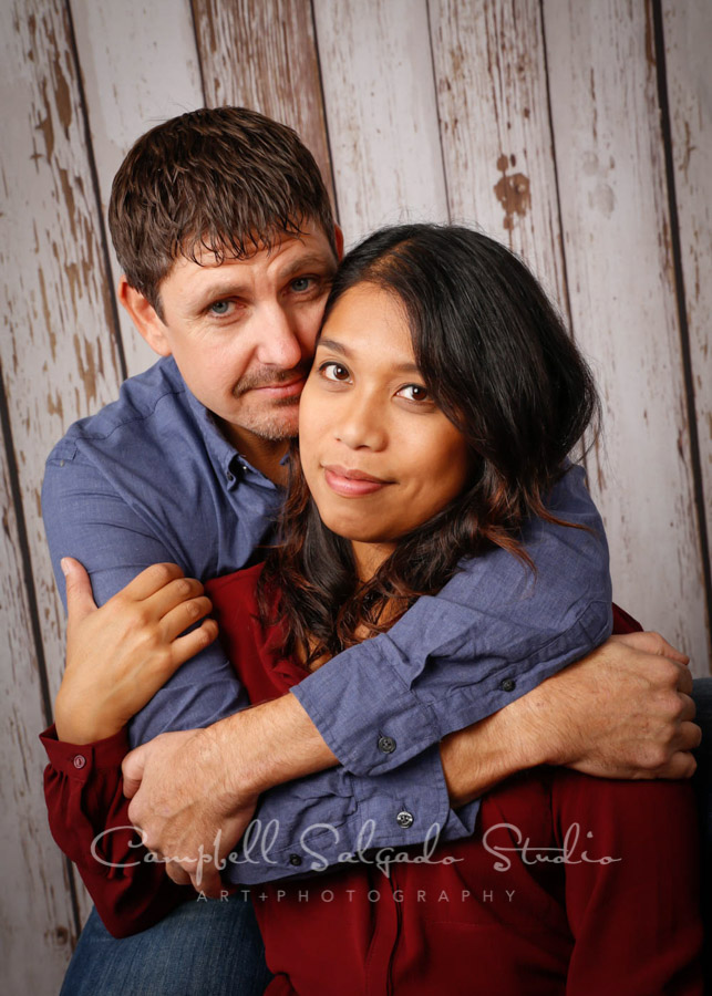 Portrait of couple on white fenceboards background by family photographers at Campbell Salgado Studio in Portland, Oregon.