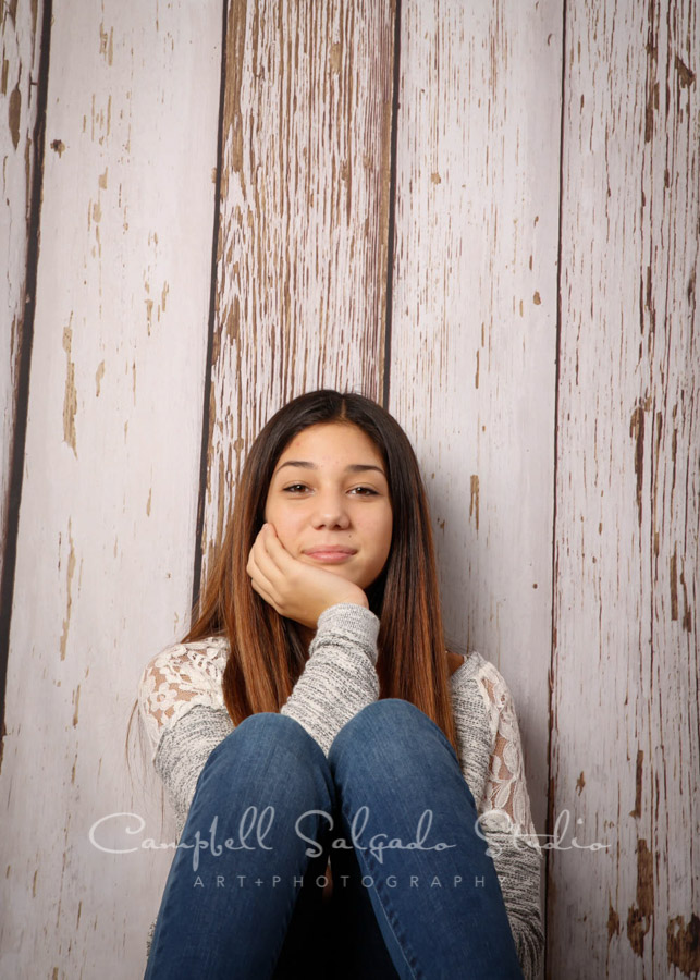 Portrait of girl on white fenceboards background by teen photographers at Campbell Salgado Studio in Portland, Oregon.