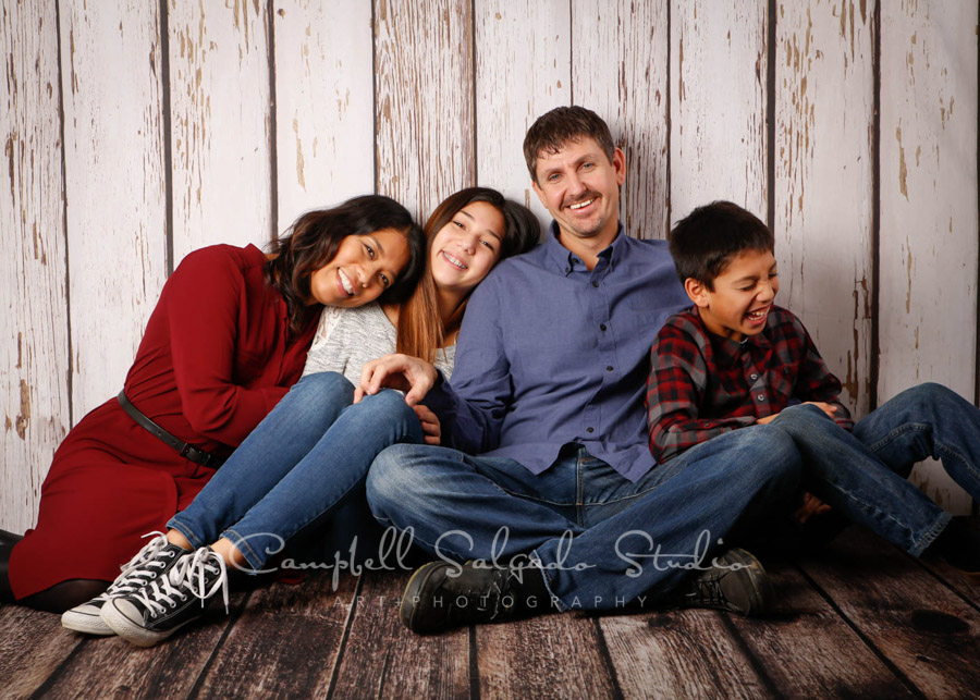Portrait of family on white fenceboards background by family photographers at Campbell Salgado Studio in Portland, Oregon.