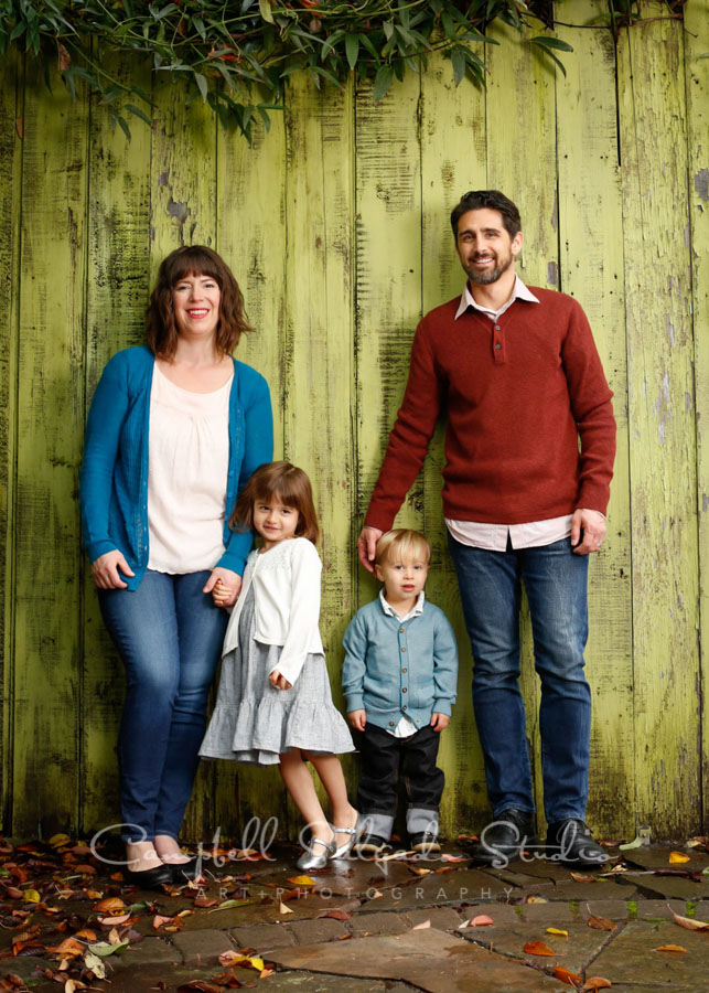 Portrait of family on lime fence boards background by family photographers at Campbell Salgado Studio in Portland, Oregon.