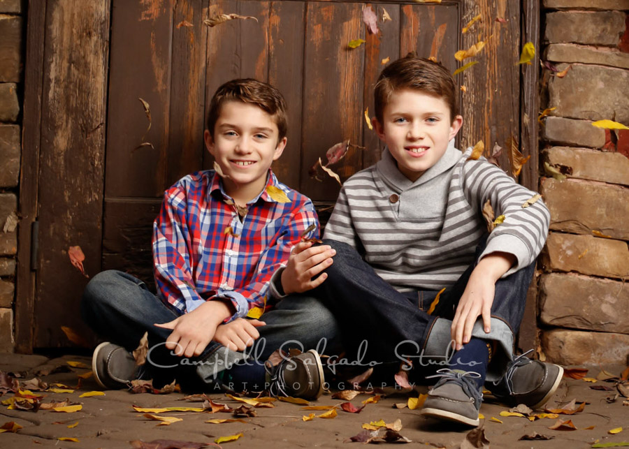 Portrait of boys on rustic door background by child photographers at Campbell Salgado Studio in Portland, Oregon.