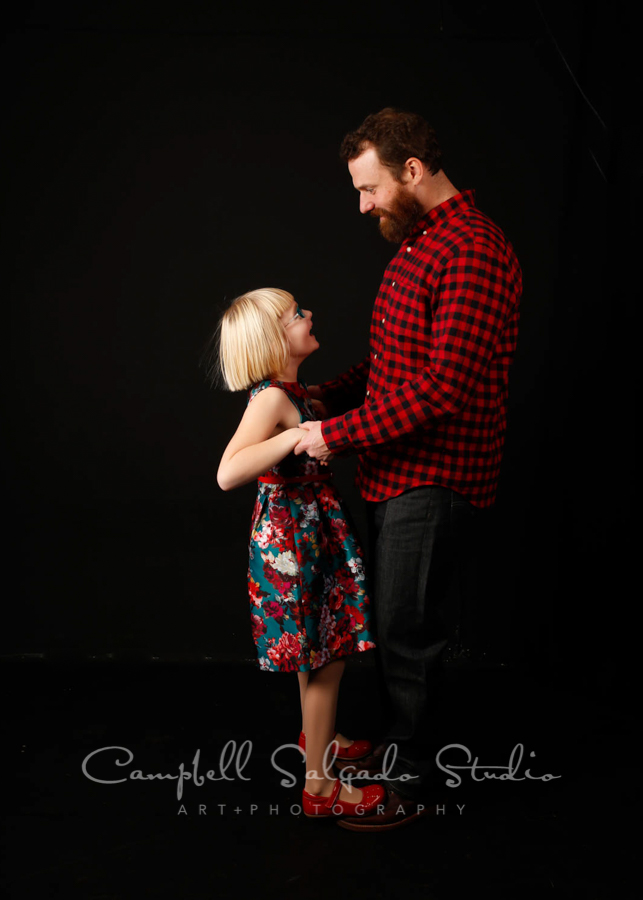 Portrait of dad and daughter on black  background  by  family  photographers at Campbell Salgado Studio in  Portland , Oregon.
