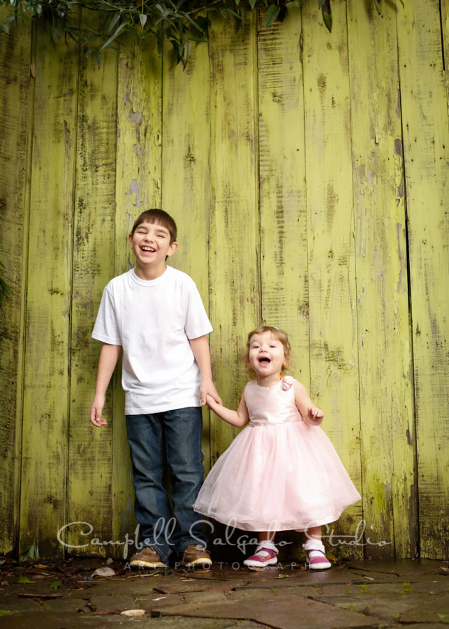 Portrait of children on lime fence boards background by child photographers at Campbell Salgado Studio in Portland, Oregon.