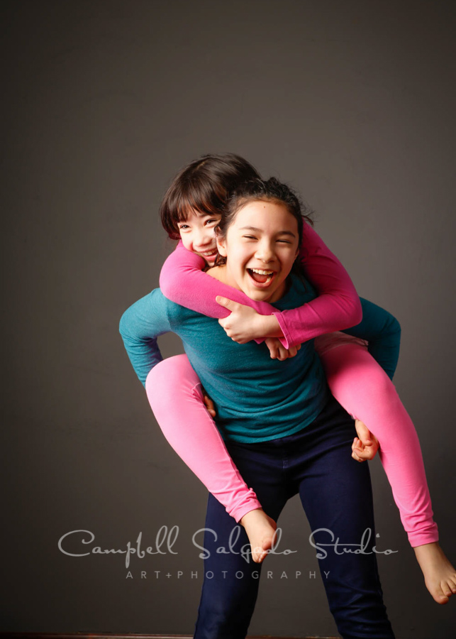 Portrait of sisters on grey background by child photographers at Campbell Salgado Studio in Portland, Oregon.