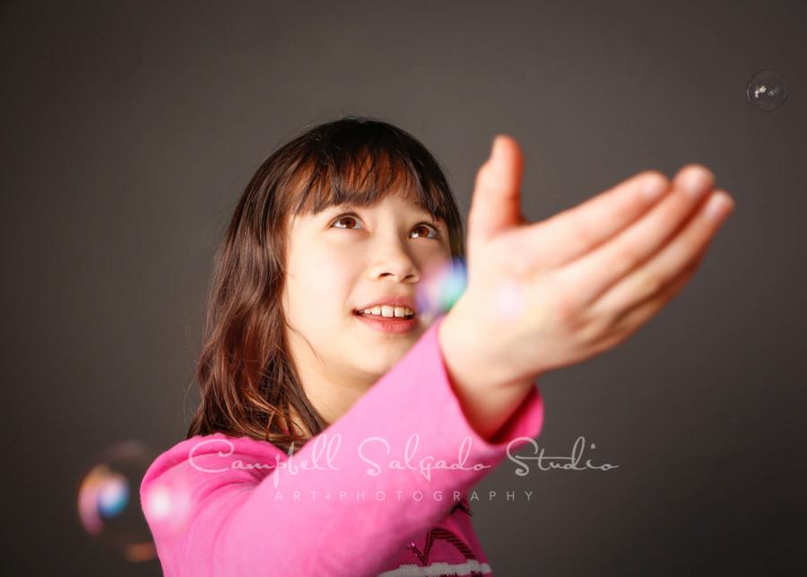 Portrait of child on grey background by child photographers at Campbell Salgado Studio in Portland, Oregon.