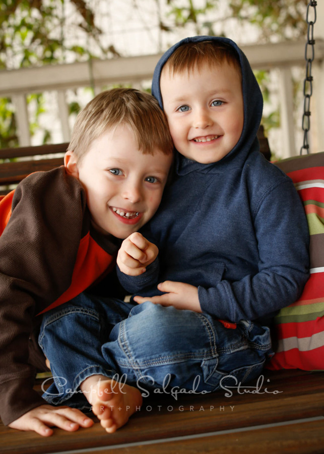 Portrait of kids on porch swing background by children's photographers at Campbell Salgado Studio in Portland, Oregon.