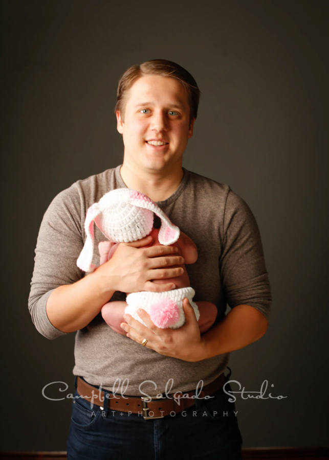 Portrait of father and baby on gray background by newborn photographers at Campbell Salgado Studio in Portland, Oregon.