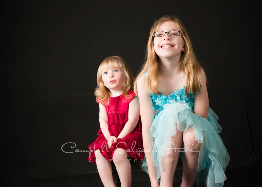 Portrait of sisters on black background by family photographers at Campbell Salgado Studio in Portland, Oregon.