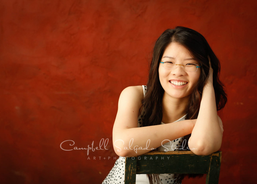 Portrait of teen on red stucco background by teen photographers at Campbell Salgado Studio in Portland, Oregon.