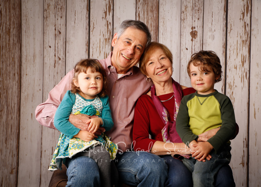 Portrait of multi-generational family on white fenceboards background by family photographers at Campbell Salgado Studio.