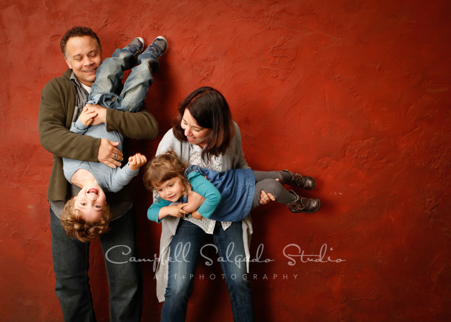 Portrait of family on red stucco background by family photographers at Campbell Salgado Studio.