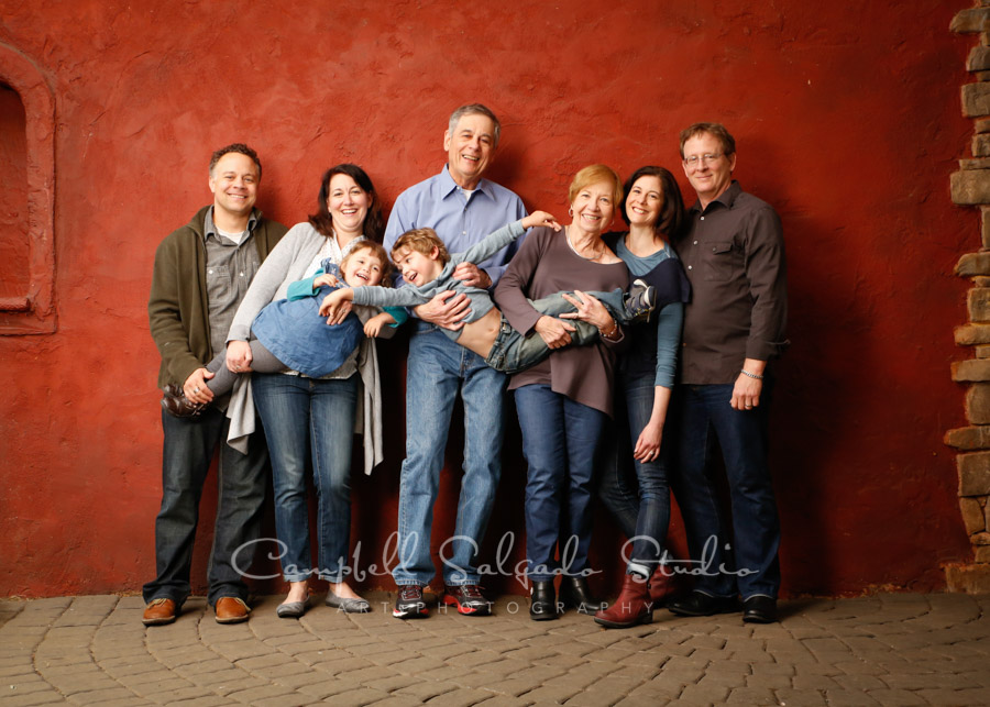 Portrait of multi-generational family on red stucco background by family photographers at Campbell Salgado Studio.