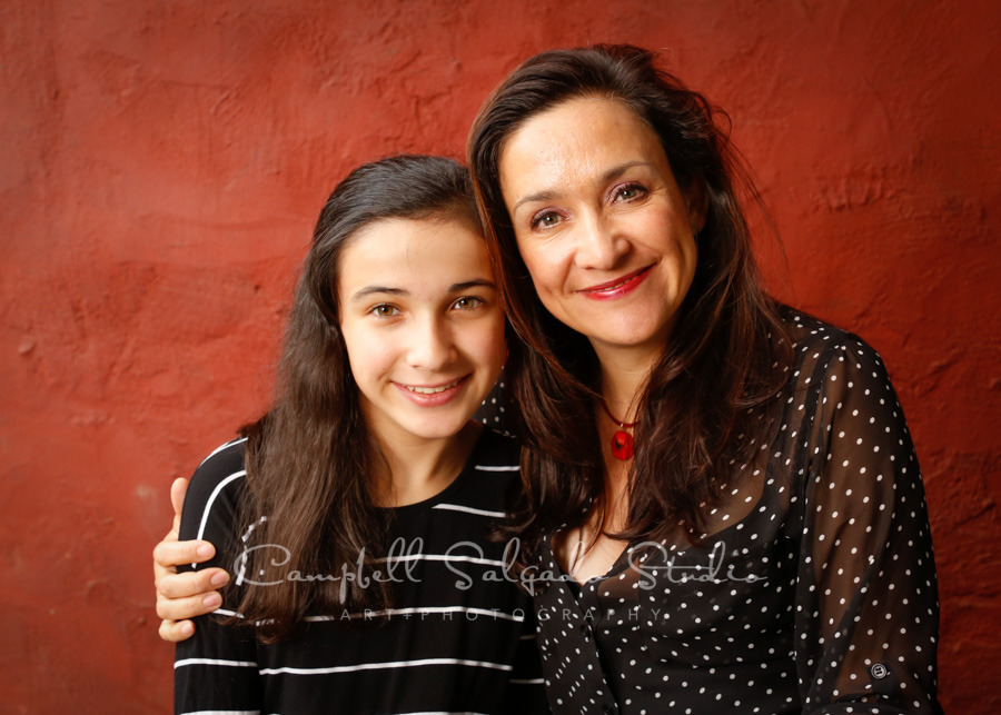 Portrait of mother and daughter on red stucco background by family photographers at Campbell Salgado Studio in Portland, Oregon.