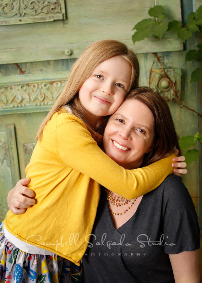 Portrait of mother and daughter on vintage green doors background by family photographers at Campbell Salgado Studio in Portland, Oregon.