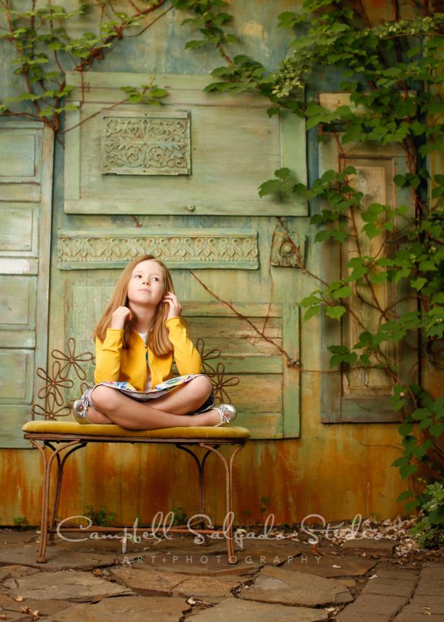 Portrait of girl on vintage green doors background by child photographers at Campbell Salgado Studio in Portland, Oregon.