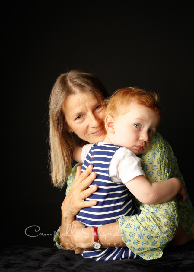Portrait of mother and son on black background by family photographers at Campbell Salgado Studio in Portland, Oregon.