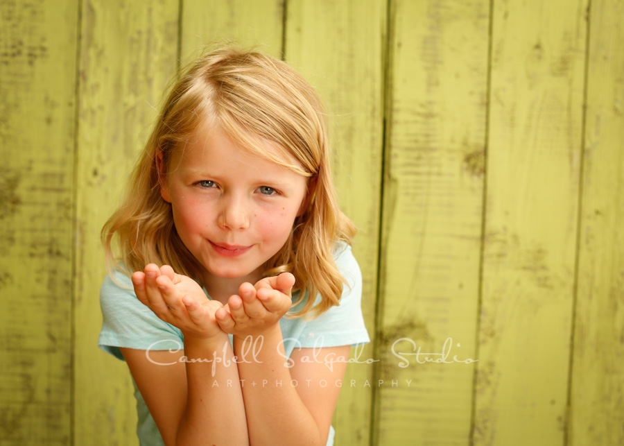 Portrait of girl on lime fenceboards background by child photographers at Campbell Salgado Studio in Portland, Oregon.
