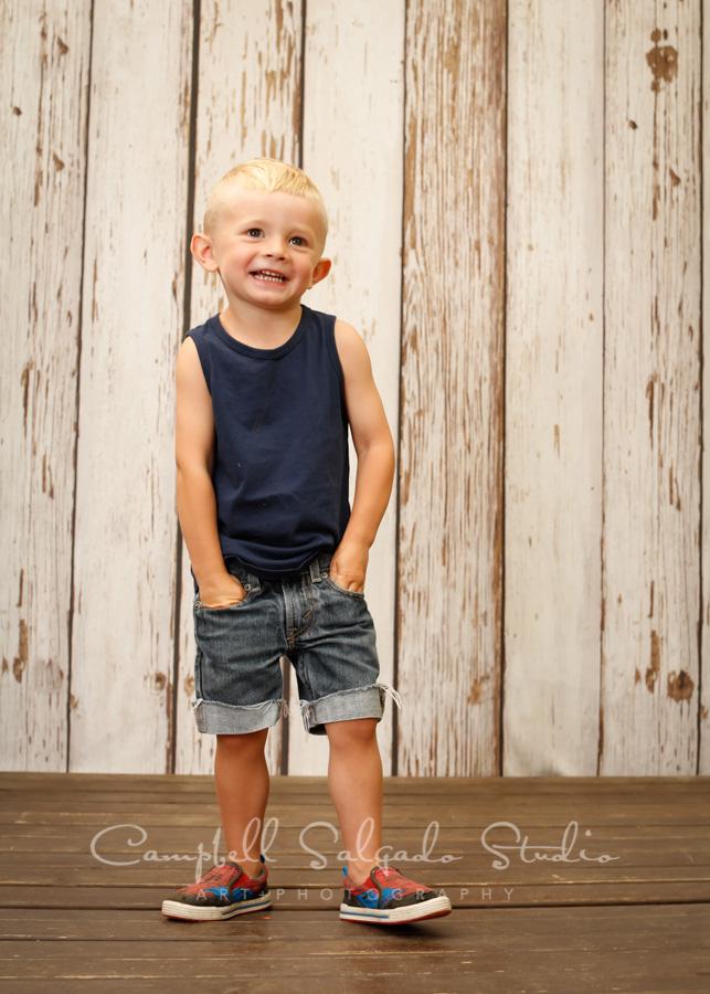 Portrait of boy on white fenceboards background by child photographers at Campbell Salgado Studio in Portland, Oregon.