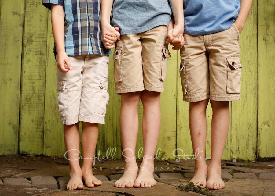 Portrait of brothers on lime fenceboards background by family photographers at Campbell Salgado Studio in Portland, Oregon.