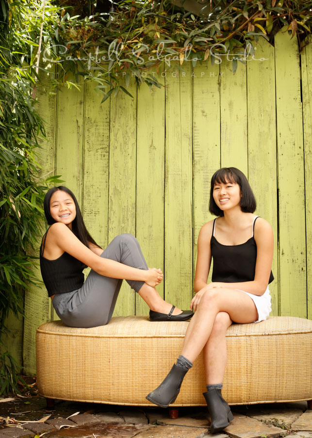 Portrait of girls on lime fenceboards background by family photographers at Campbell Salgado Studio in Portland, Oregon.