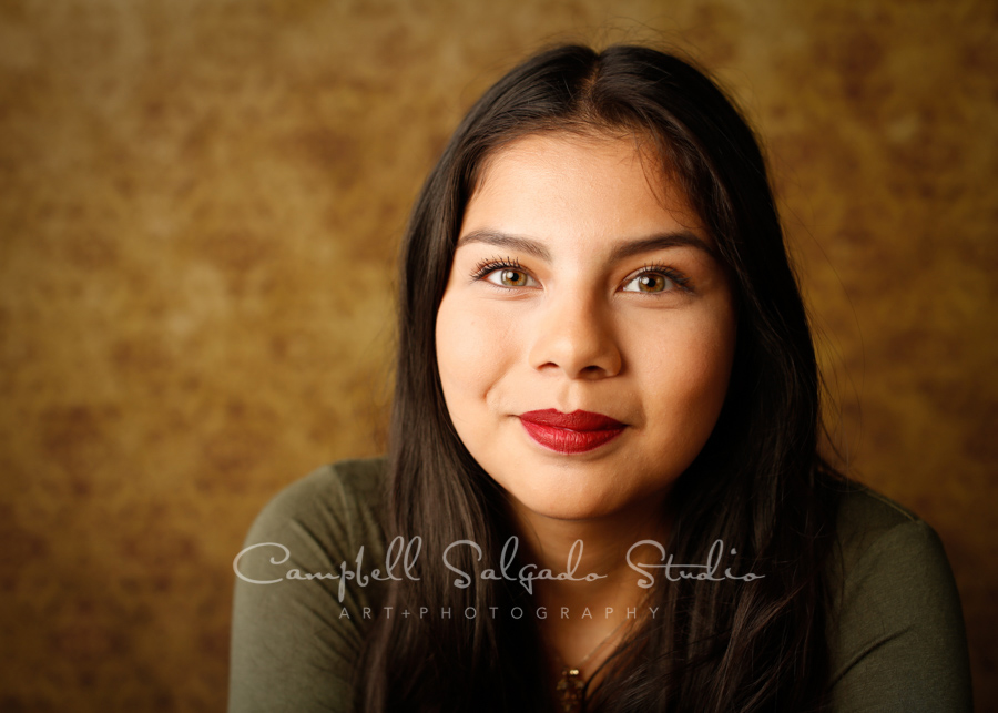 Portrait of teen on amber light background by teen photographers at Campbell Salgado Studio in Portland, Oregon.